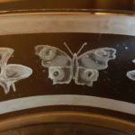 Vlinders en bloemen diep gegraveerd, boven- en  onderrand geëtst